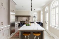 Beautiful contemporary kitchen features two counter stools with curved woods seats tucked sat under a stunning limed oak island topped with honed white marble countertops and fitted with a sink and polished brass gooseneck faucet lit by three vintage glass pendants.