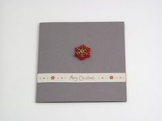 Red Snowflake - A beautiful and versatile folded card made from the highest quality coloured card. Its pure solid colour flows through its surface which features a crisp, original smooth finish. Design features a mounted plywood & felted snowflake and as finishing touch printed ribbon runs through the front of the card saying: 'merry christmas'.