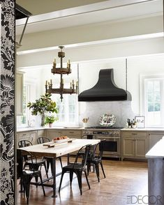 Marble backsplash behind stove. Painted cabinets. Metal chairs