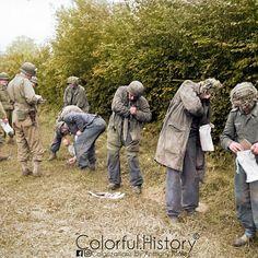 Fallschirmjägern (paratroopers) of the Luftwaffe 3.Fallschirmjäger-Division (3.FJD) are taken prisoner and empty their pockets in a bag along a hedge under the care of several GI's - Hill 192, commune of Saint Georges D'Elle (near Saint-Lo), Normandy, France, June 1944
