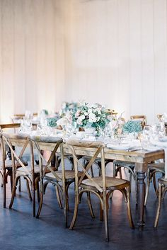wedding table decorations bouquets of flowers with white roses and lots of greenery on a brown wooden table mariel hannah
