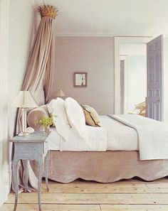 sooo gorgeous ! bedside table + bed skirt + cozy neutrals + painted door + wide wood plank flooring in natural stain.