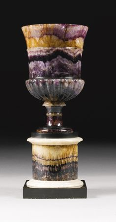 A George III Blue John vase.. From the Blue John Cavern in Derbyshire near the City of Sheffield circa 1800 with gadroon carving, on a turned socle and circular column with white marble ornament raised on a square black Ashford marble plinth