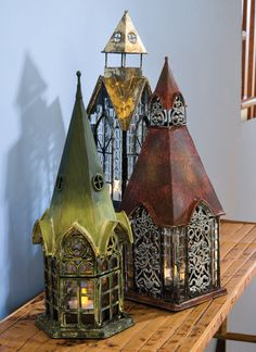 """Architectural Lanterns.            Overview      Product Detail    Architectural Lanterns  Combining design elements from days gone by—fancy metalwork, Gothic arches, beveled glass—these lanterns are romantic and fanciful, like little fairy houses. LED tea lights are recommended to avoid over-heating (sold separately). Each is metal and glass, about 12"""" high. As shown left to right: Durham, or Devonshire, Ellington.    Buy 2 or more, $26.95 each"""