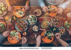 Enjoying dinner with friends. Top view of group of people having dinner together while sitting at the rustic wooden table - stock photo
