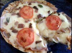 Receita de Pizza de Frigideira - 1 disco de Rap10, 2 colheres de molho de tomate, 80 gramas de presunto, 80 gramas de mussarela, 30 gramas de bacon picadinho, 3 rodelas de tomate, folhas de manjericão (q.b.)