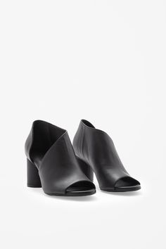 Made from smooth leather with minimal detailing, these asymmetric leather shoes have a high round heel. Cut out on each side, they have an open toe and cushioned leather insole.