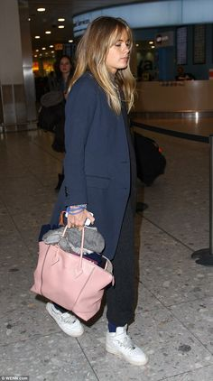 Cressida wore cashmere jogging bottoms and a pair of white high-top trainers at Heathrow today