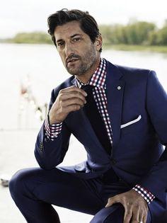 Rojo de la camisa a cuadros resalta el tono azul del traje