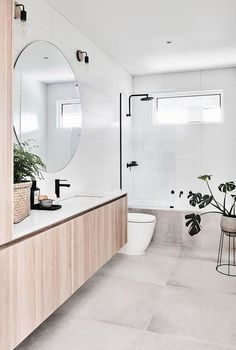 Accessorise your bathroom a large circular mirror for a Scandi-inspired look. Add in greenery to add extra life to the room.