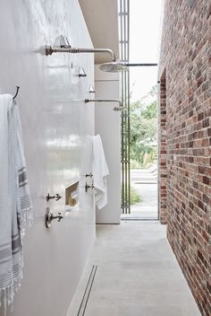 Tadelakt and brick walls contrast each other in this pool house shower design. #poolhouse #outdoorshower #exposedbrick