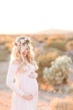 Gorgeous sunset desert maternity session. Blush rose floral crown. Blush off-the-shoulder full length dress for mamma to be. Soft blue sports jacket for dad. And stunning golden desert light.