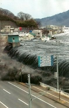 Black with muck scoured from the harbor, the first tsunami wave pours over a seawall in Miyako, carrying vans and boats.