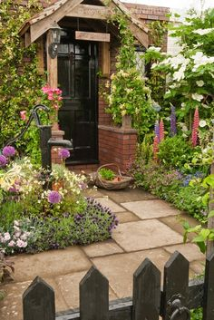 I love this adorable garden entryway behind a picket fence.