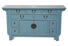 Five feet wide and boasting traditional brass hardware as well as a marble inlay top, this buffet will make a majestic style statement. In addition to cabinets behind the central double doors, it has nine drawers of various sizes to keep smaller items organized. The gently distressed blue finish accentuates the buffet's classical form.