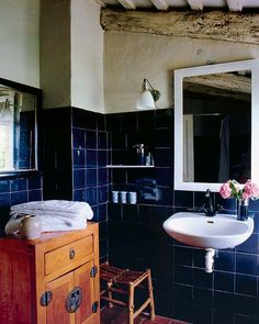 rustic royal blue tiles + pink flowers+ textured cream wall + simple mirror frame + brown cabinet