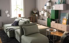 A living room is styled with modular sofas and lots of wall storage.