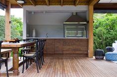 A mistura de estilos fica por conta da churrasqueira, em inox, instalada em pleno ambiente rústico de madeira Foto: Divulgação: Marília Veiga Interiores