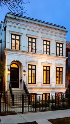 Neoclassical row house with limestone exterior accented with black framed windows, arched black front door lit by wall lanterns and black iron railings along the stairs and front of the house. Classic Architecture, Architecture Design, Neoclassical Architecture, Revival Architecture, Exterior Tradicional, Design Exterior, Facade Design, Black Exterior, Exterior Paint