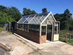 long greenhouse on dwarf wall