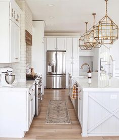 white kitchen, large gold light fixtures in kitchen, painted brick in kitchen, white brick in kitchen, bright kitchen, mixed metals in kitchen