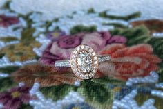 An oval shaped diamond, a rose gold halo with round brilliant diamonds and side diamonds set in a white gold band,