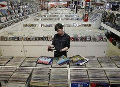 福特市 Ford City 一家唱片店,工作人员正在检查货柜上的黑胶唱片,美国 US 新泽西州 New Jersey。据美国数据调查公司 SoundScan 统计,2014年全球黑胶唱片总销量为920万张,比2013年增长52%,创1991年有记录以来最高值。摄影师:Mel Evans