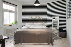 Wyraziste czarno-białe pasy tapety maskują nieregularny kształt pomieszczenia i optycznie je poszerzają. W ich tło dyskretnie wtopiła się półeczka na dekoracje, do której przymocowano praktyczne kinkiety na klipsach. Pozostałe ściany ozdobiono czarno-białymi grafikami.