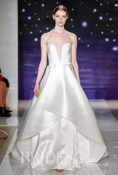 Brides.com: . Strapless silk crepe plunging ball gown with layered gazar skirt detail, Reem Acra