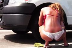A car wash is employing women to soap down and rinse cars with their bikinis only.