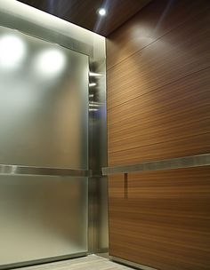 Premier Elevator utilized natural wood veneer wall and ceiling panels stained to match lobby stone walls harmonizes this commercial space. Frosted glass side walls capture and reflect light making the elevator interiors seem larger and more spacious.