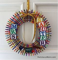 "8"" embroidery hoop placed inside 12"" embroidery hoop, box of 64 crayons, space all crayons evenly across two hoops and hot glue in place. Hang from ribbon fixed to 12"" hoop. Letter are stickers or charms for scrapbooking. Great Christmas Gift for Teachers"