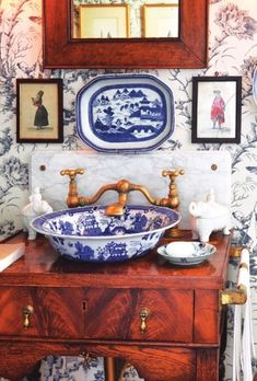 Room of the Day ~ blue porcelain sink and plate, miniature art, wood cabinet and gorgeous wallpaper in this fetching blue and white bath
