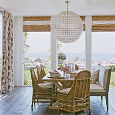 Beach dining room features oversized Capiz shell orb light, wood floors and floor to ceiling windows: CoastalLiving.com