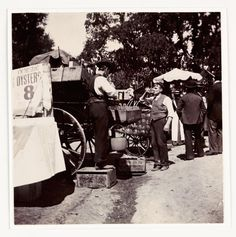 c. 1890-1910: Victorian Revellers at London's 'Appy 'Ampstead c. 1898  A man takes a cooling drink from a stall. The vendor stands nearby on a crate. On the left a sign for oysters reads 'A'int they grand?' At the time, oysters were a popular cheap snack.