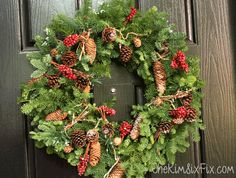 A pretty Christmas front door, featuring wood slice artwork, with natural garlands, pine cones, and pops of red with an old sleigh and some lanterns. A great look for all winter.