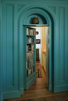 teal wall bookcase is actually a secret door to a hidden room