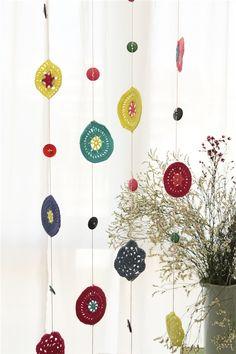 Paso a paso para hacer esta cortina de ganchillo que combina colores alegres en lana y botones.