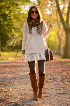 Cool layered outfit. White lace tunic, oversized sweater featuring a simple graphic pattern, leggings, leopard scarf, wide knee-high leather boots, Louis Vuitton handbag.