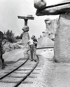 """Walt Disney stands on the train tracks that pass through Balancing Rock Canyon in the vintage,  """"Nature's Wonderland"""" attraction at Disneyland."""