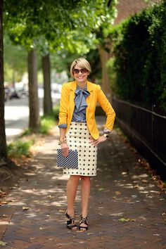 polka dot pencil skirt, tie neck blouse, yellow colored blazer, clutch, work outfit