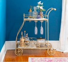 """There's also her mother's """"tea cart,"""" repurposed as a bar cart in the dining room. The cart was originally white, but Danielle repainted it to compliment the mixed metal design of the house; """"It's a perfect addition to the space. Looking For Houses, Bar Cart Styling, Tea Cart, Walnut Dining Table, Wood Headboard, Wood Beams, Modern Bohemian, Beautiful Space, Home Look"""