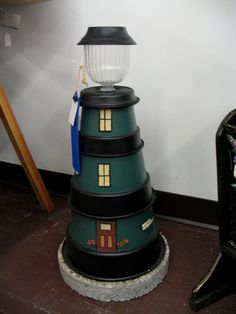 Solar light house made from three different size pots one pot saucer and a stepping stone.