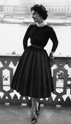 elizabeth taylor - unusually understated here, yet elegant as always 50s black day dress skirt sweater wool winter black full skirt belt shoes vintage fashion icon style movie star found photo portrait