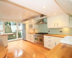 Image result for cream kitchen with blue tiles and wooden worktop
