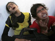 Palestinian girls cry after their father was killed in a UN-operated school after an alleged Israeli attack in Beit Hanun town, northern Gaza strip