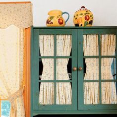 Interior Curtains- Mimic cafe windows by adding curtains to glass-front cabinets. Fold fabric in 1-inch pleats before stapling the top and bottom to the inside of the door. Cinch in the middle with matching fabric straps. thisoldhouse.com | from Easy Kitchen Cabinet Makeovers