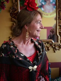 Mari Carmen Onrubia de Esquivias dressed in another one of her fabulous flamenco dresses with a superb hand-embroidered vintage mantón de Manila shawl (made in Spain, but named for Manila), held in place by a lovely butterfuly pin, Caseta Los Nietos de Don Manuel, Feria de Sevilla, April 14, 2016.  Mari Carmen has a different dress and differnet shawl for every day of the Feria.  Photo by Gerry Dawes©2016, Canon M3