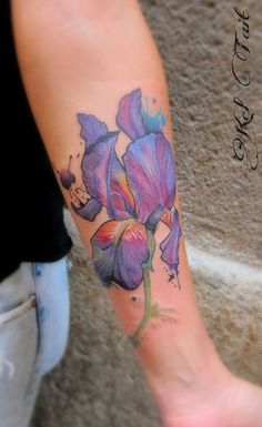 Beautiful watercolor iris tattoo done on womans forearm by Kel Tait
