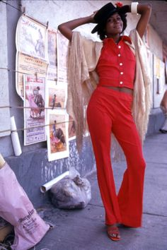 Carol Hobbs poses on a sidewalk, dressed in bright red top and trousers, a tan shawl over her shoulders and a bolero hat in Mexico, 1972.